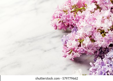 Lilac flowers on marble background. Copy space. Top view.