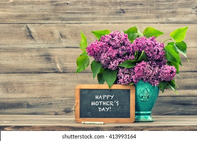 Lilac flowers and vintage blackboard with sample text Happy Mothers Day! Vintage style toned picture. Mother's Day greetings card. Vintage still life. Mother's day. Mothers Day gift. Mothers Day