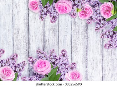 Lilac flowers with wild roses on background of shabby wooden planks