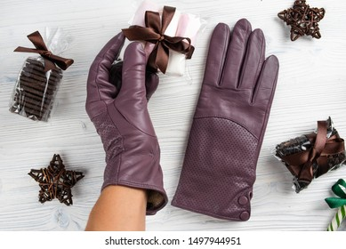 lilac leather gloves on a wooden table defiantly worn on a woman's hand