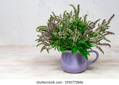 Lilac mint flowers with green leaves in a lilac cup on a white wooden background. Homemade herbs for tea. Place for an inscription.