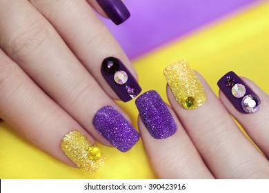 Lilac purple manicure with gold glitter and rhinestones in different colors on a purple background.
