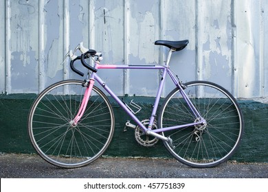 Lilac sports bike standing near rifle-green wall