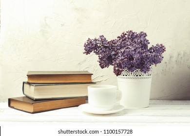 Lilac in white decorative bucket, stack of books, white cup with coffee on white stone background.