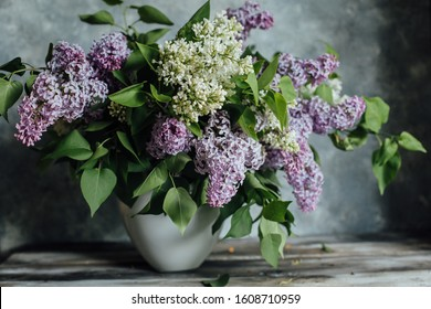 Lilacs in a white vase on a grey wooden background. Selective focus.