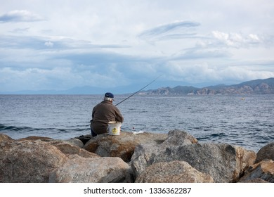 L'ILE-ROUSSE, HAUTE- CORSE/FRANCE - OCTOBER 31, 2018: A man is fishing on the rocky shore of the Mediterranean Sea