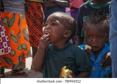 LILIACHI, ZAMBIA - CIRCA 2017 - An unidentified African child with flies on his face eats some bread circa 2017 in Liliachi, Zambia.