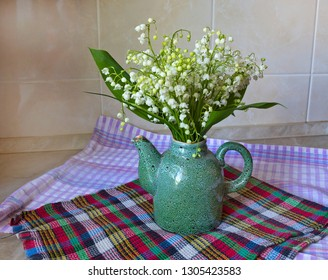 Lilies of the valley bouquet in a ceramic teapot