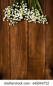 Lilies of the valley on a brown wooden background with copy space - vertical photograph.