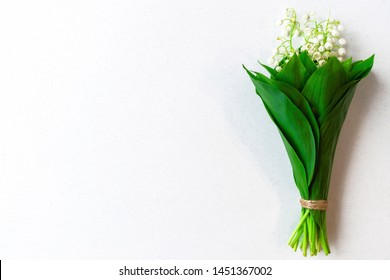 Lilies of the valley on white background. Flat lay with flovers and place for your text. Top view mockup