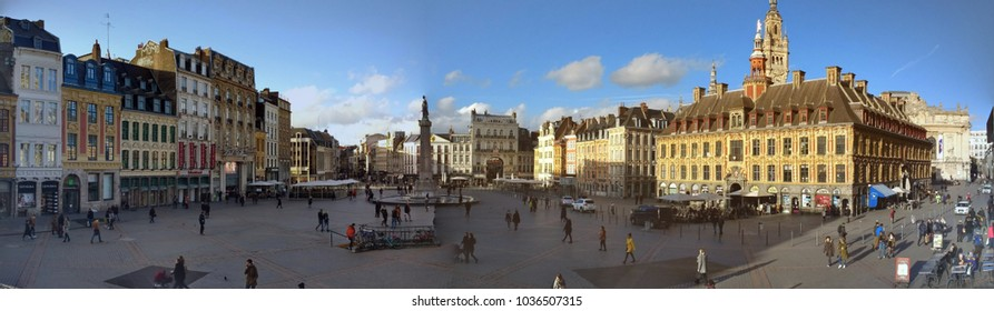 Lille France February 15 2018: panoramic view of Grand Place, city central square from the Theatre du Nord with monument, old stock exchange building, shops with people walking to work & on holiday