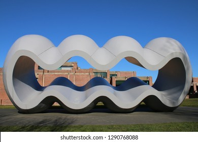 Lille France - February 16 2018: Richard Deacon twentieth century metal art sculpture wave smooth rhythmic tubular form foreground of the Metropole Museum of Modern contemporary and Outsider Art