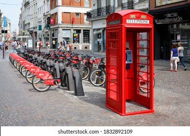 LILLE, FRANCE - July 18, 2013. Red British telephone box and free bike rental station in a street in Lille, France