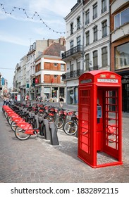 LILLE, FRANCE - July 18, 2013. Free bike rental station and red British telephone box in a street in Lille, France