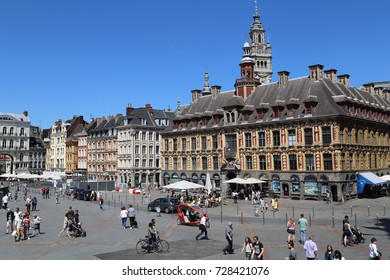 Lille, France - May 26, 2017: Young tourists walk on the Place du General de Gaulle square in front of the old Stock Exchange building in Lille, France on May 26, 2017