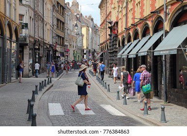 Lille, France - May 27, 2017: Tourists walk pasts the shops in the Rue de la Monnaie street in the old part of Lille, France on May 27, 2017