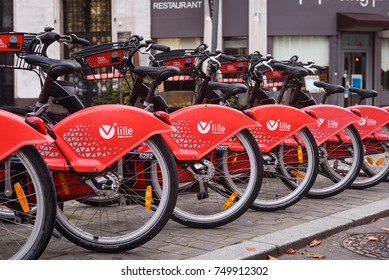 LILLE, FRANCE - OCTOBER 28, 2017: Red bikes for hire in Lille. The V Lille libre service is based on Velib bikes in Paris where everyone can rent public bicycles. Bike station in Lille, France