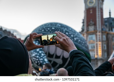 Lille,FRANCE-May 04,2019: Man who makes videos and photos with a mobile phone on the great carnival parade Eldorado Lille 3000.Lille 3000 is an association representing a cultural program.