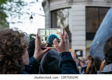 Lille,FRANCE-May 04,2019: Man who makes videos and photos with a tablet on the great carnival parade Eldorado Lille 3000.Lille 3000 is an association representing a cultural program.