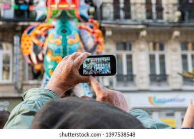 Lille,FRANCE-May 04,2019: An older man is making video on a mobile phone at the great carnival parade Eldorado Lille 3000.Lille 3000 is an association representing a cultural program.