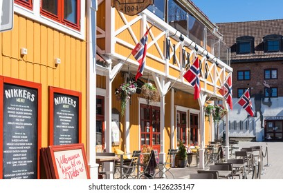 Lillehammer, Norway - August 5 2018: Colorful wooden building with Norwegian flags in Lillehammer