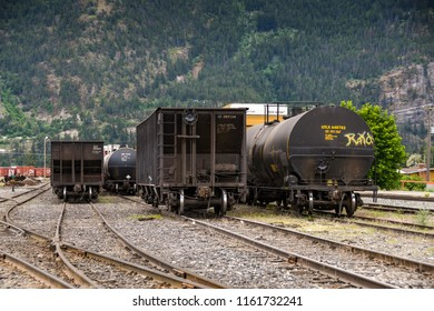 LILLOOET, BRITISH COLUMBIA,  CANADA - JUNE 2018: Freight wagons and an oil tanker in the railway yard in Lillooet, British Columbia.