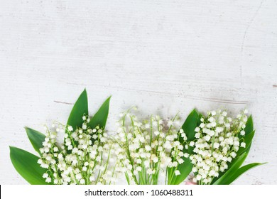 Lilly of the valley flowers with green leaves border on white wooden background