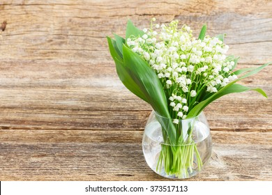Lilly of valley in glass vase on wooden table