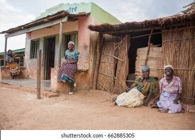 LILONGWE, MALAWI - SEPTEMBER 04 2009: African Malawian women, dressed in traditional wear, gather outside their brick buildings and grass shacks to eat, socialize and do their daily chores.