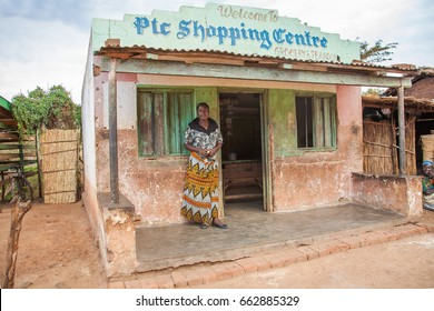 LILONGWE, MALAWI - SEPTEMBER 04 2009: An African Malawian woman in traditional African clothing, made from bold-patterned fabric, stands outside a typical rural grocery shop near Lilongwe in Malawi.