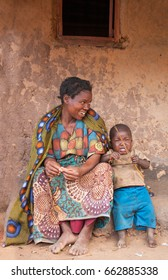 LILONGWE, MALAWI - SEPTEMBER 04 2009: An African Malawian mother and toddler sit outside a traditional brick built house, wearing traditional clothing made from bold patterned African fabric.