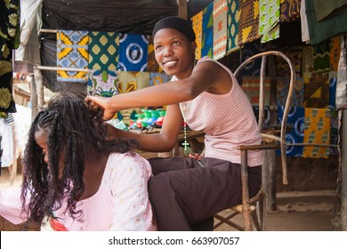 LILONGWE, MALAWI - SEPTEMBER 05 2009: A basic Malawian street side hair salon. Here the hairdresser is creating braids in her clients hair. A typical request in Malawi.