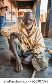LILONGWE, MALAWI - SEPTEMBER 05 2009: An old African Malawian man in ragged clothing sits outside a dilapidated shop in Malawi.