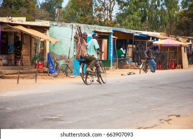 LILONGWE, MALAWI - SEPTEMBER 05 2009: A typical Malawian street scene with traders and people on bicycles carrying their wears. In this case, fresh fish from the market.