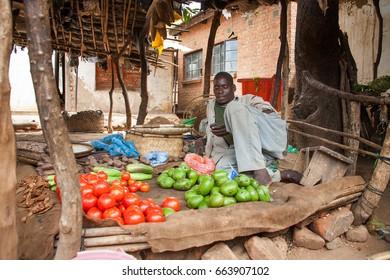 LILONGWE, MALAWI - SEPTEMBER 05 2009: An African Malawian man selling fresh produce at a local street food market.