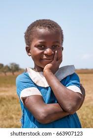 LILONGWE, MALAWI - SEPTEMBER 05 2009: An African Malawian school girl on her way home from school in ragged school uniform.