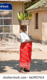 LILONGWE, MALAWI - SEPTEMBER 05 2009: An African Malawian woman carries corn in a basin on her head. Women in Malawi are able to carry and balance heavy loads on their heads for long distances.