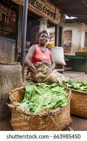 LILONGWE, MALAWI - SEPTEMBER 05 2009: An African Malawian woman sells leafy greens at a typical Malwaian street food market near Lilongwe.