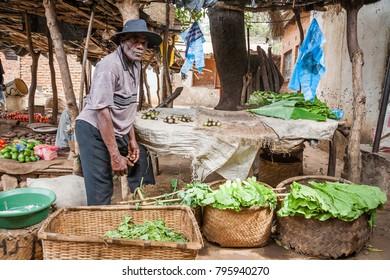LILONGWE, MALAWI - SEPTEMBER 05 2009: An African Malawian man selling fresh produce at a rural food market.
