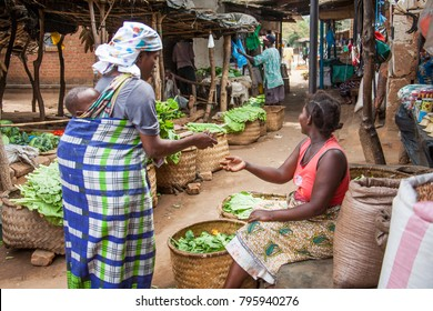 LILONGWE, MALAWI - SEPTEMBER 05 2009: An African woman carrying her baby on her back, pays for her greens at a rural market.