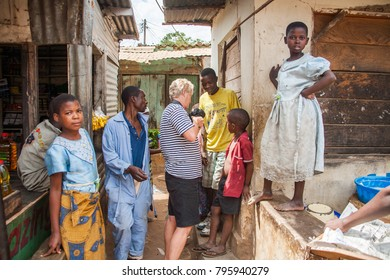LILONGWE, MALAWI - SEPTEMBER 05 2009: Malawian children looking at photos on tourist's camera in a local market.