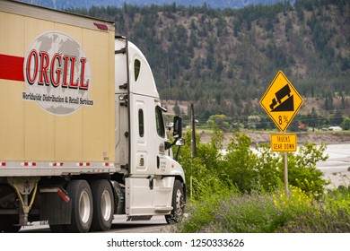 LILOOETT, BRITISH COLUMBIA, CANADA - JUNE 2018: Large freight ruck passing a sign on the road side in Lilooett warning drivers of a steep hill.