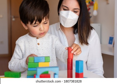 Liltle Preschooler Kid playing with wood blocks and teacher educador help using face mask for coronavirus pandemic. Homeshooling. Learning Community. Montessori School