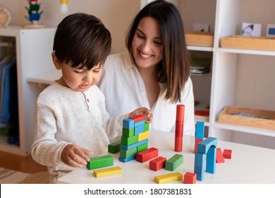 Liltle Preschooler Kid playing with wood blocks and teacher educador help. Homeshooling. Learning Community. Montessori School