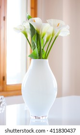 Lily of the Nile (Zantedeschia aethiopica) flowers in a white vase. Photography very bright.