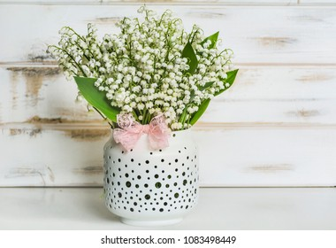 Lily of the Valley Bouquet in  Vase with Pink Ribbon .Spring Flowers Background