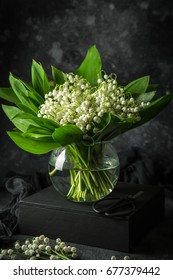 Lily of the valley flowers in glass vase, black background,  selective focus