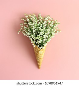Lily of the valley flowers  -  spring flowers on waffle cone. Pastel pink background.