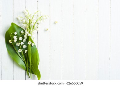 lily of the walley flowers on white wood table, wedding background