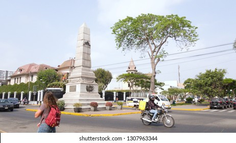 Lima, Barranco / Peru - 12.18.2018: This is a Malecon Saenz Peña Park in Barranco. The photo features an old monument, a big tree, a girl walking with a red bag and a motorcycle driver.